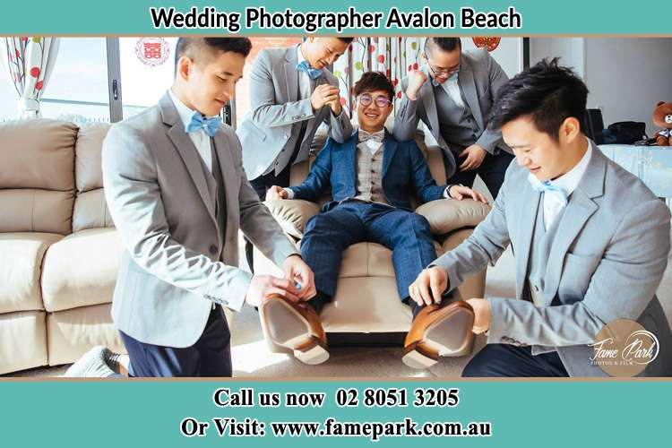 Photo of the Groom helping by the groomsmen getting ready Avalon Beach NSW 2107