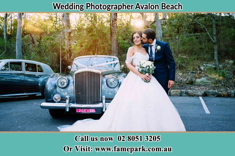Photo of the Bride kiss by the Groom at the front of the bridal car Avalon Beach NSW 2107