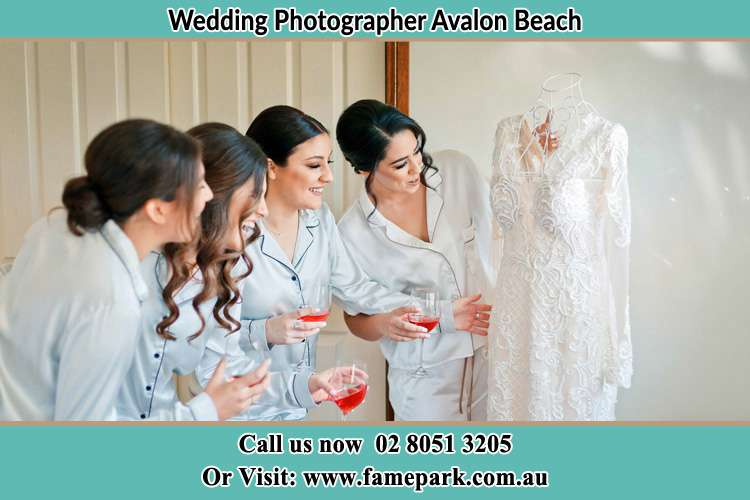 Photo of the Bride and the bridesmaids looking at the wedding gown Avalon Beach NSW 2107