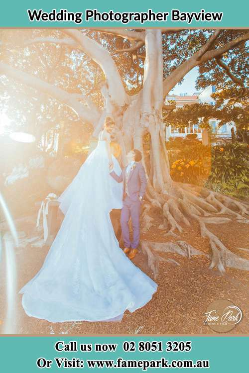 Photo of the Bride and the Groom looking each other besides the tree Bayview NSW 2104