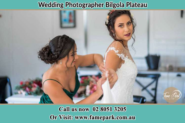 Photo of the Bride helping by the bridesmaid fitting her wedding gown Bilgola Plateau NSW 2107