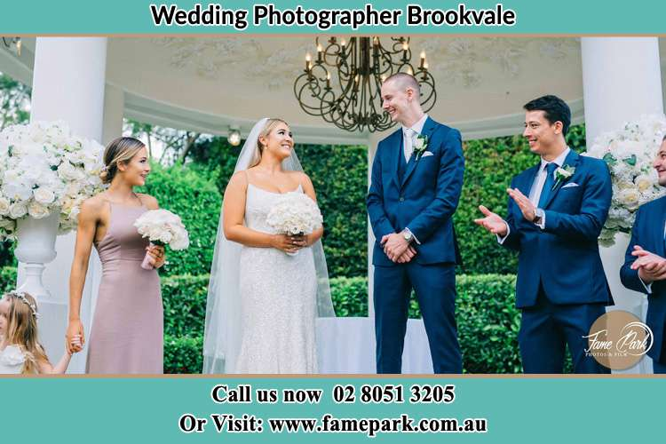 Photo of the Bride and the Groom happily looking each other with the secondary sponsors Brookvale NSW 2100