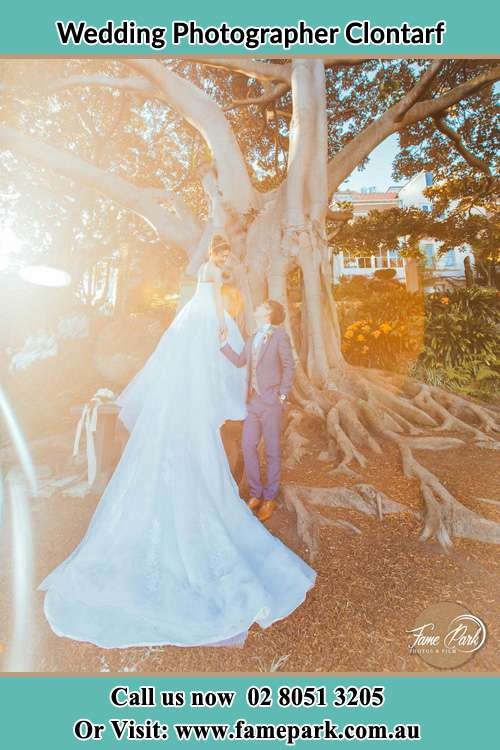 Photo of the Bride and the Groom looking each other besides the tree Clontarf NSW 2093
