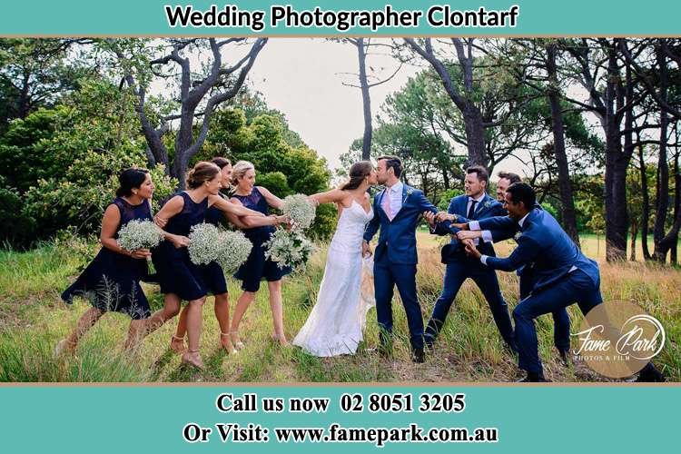 Photo of the Groom and the Bride kissing with the entourage teasing them Clontarf NSW 2093