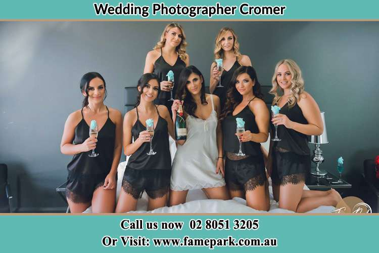 Photo of the Bride and the bridesmaids wearing lingerie and holding glass of wine on bed Cromer NSW 2099