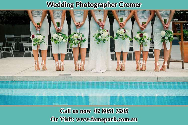 Behind photo of the Bride and the bridesmaids holding flower near the pool