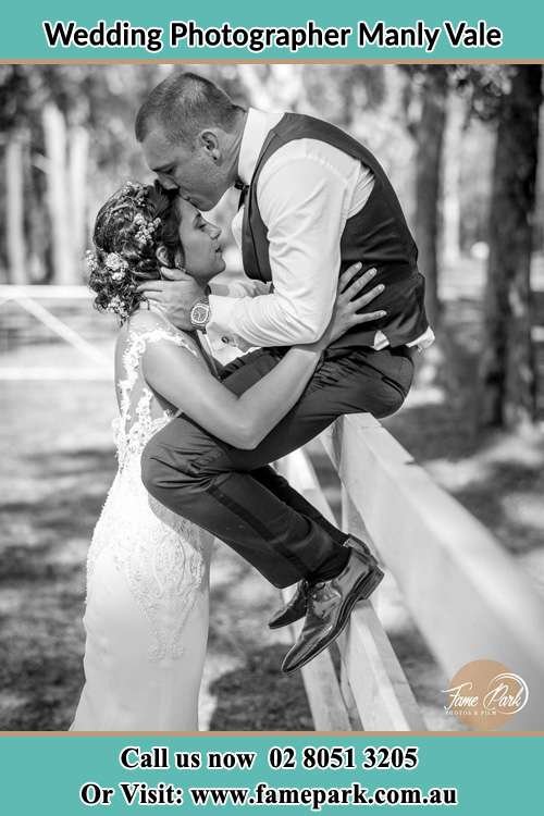 Photo of the Groom sitting on the fence kissing the Bride at the forehead Manly Vale NSW 2093