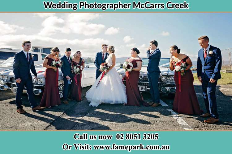 Photo of the Groom and the Bride kissing with the entourage McCarrs Creek NSW 2105