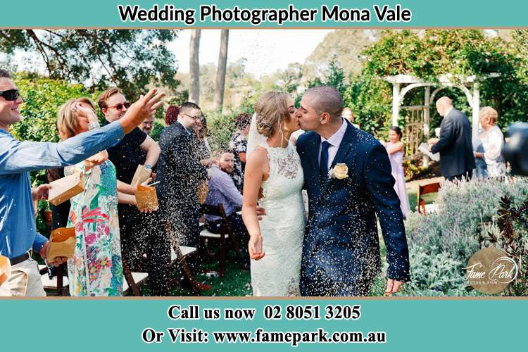 Photo of the Bride and the Groom kissing while showering rice by the visitors Mona Vale NSW 2103