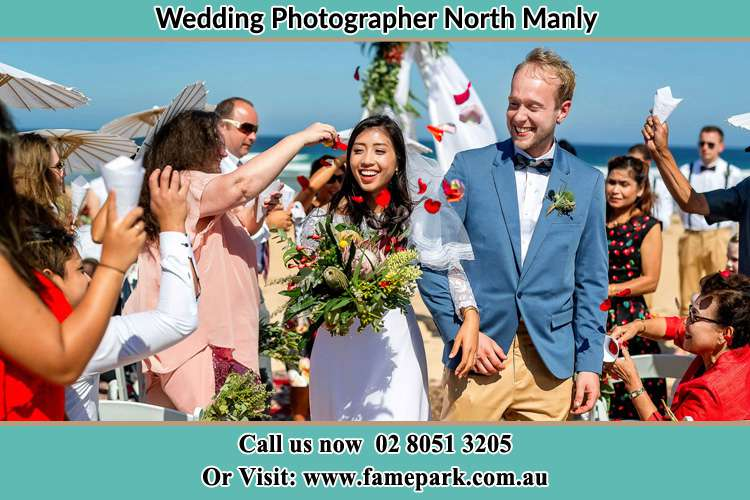 Photo of the Bride and the Groom showering flower petals by the visitors North Manly Beach NSW 2100