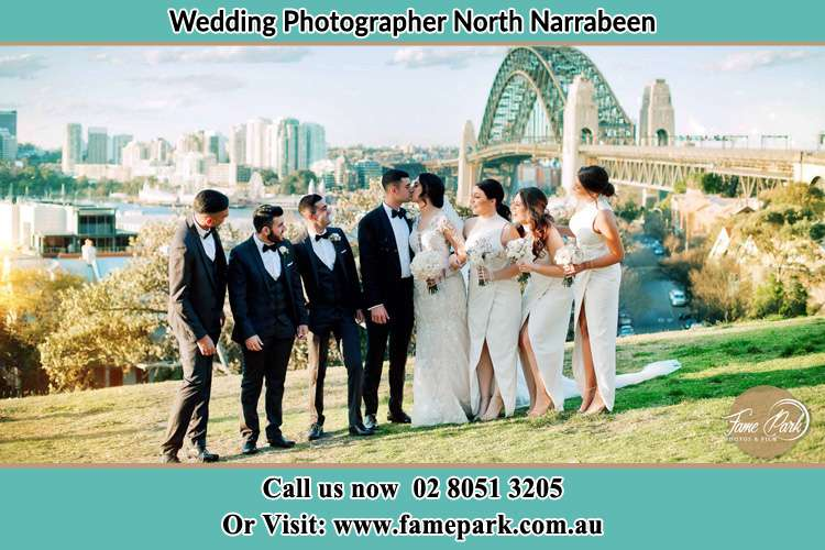 Photo of the Groom and the Bride kissing with the entourage near the bridge North Narrabeen Beach NSW 2101