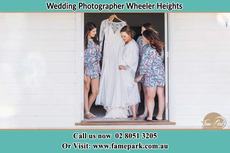 Photo of the Bride and the bridesmaids checking the bridal gown at the door Wheeler Heights NSW 2097